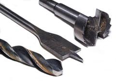 three drill bits - twist drill bit, spade drill bit, and forstner drill bit